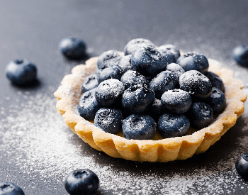 A picture of a tartlet pie that contains blueberries