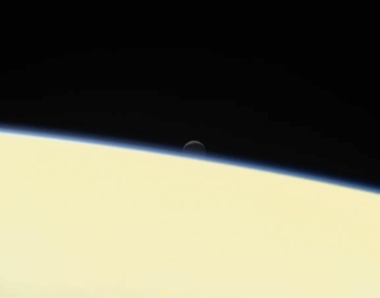 A photo of Enceladus setting behind the planet Saturn.
