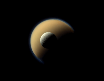 A photo of the Rhea moon in front of the Titan moon.