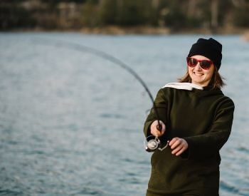 A picture of a woman catching a fish in a lake