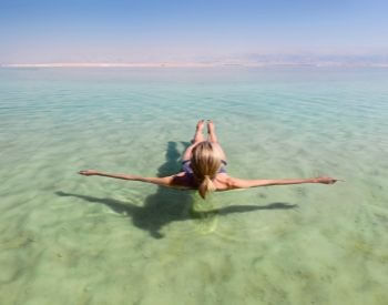 A picture of a woman floating on the surface of the Dead Sea