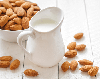 A picture of a glass of almond milk and almonds