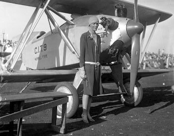 A picture of Amelia Earhart standing next to an airplane