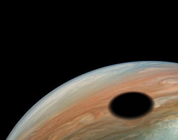 A photo of Io's shadow casted on Jupiter.
