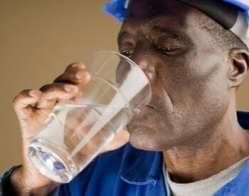A picture of someone drinking water to stay hydrated after hard work