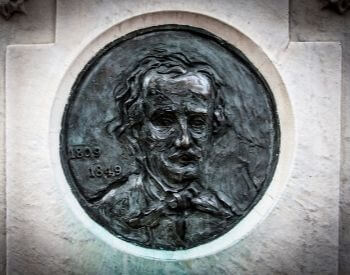 A picture of the self-portrait cast of Edgar Allan Poe on his tombstone