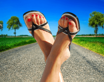 A picture of human feet in sandals