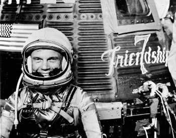 A photo of John Glenn in front of the Friendship 7 Mercury spacecraft