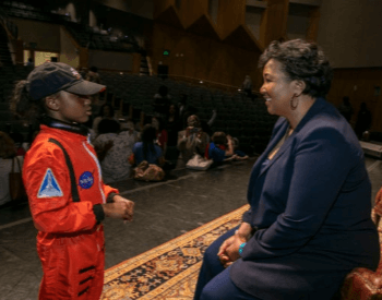A photo of Mae Jemison speaking with a second grader at an event