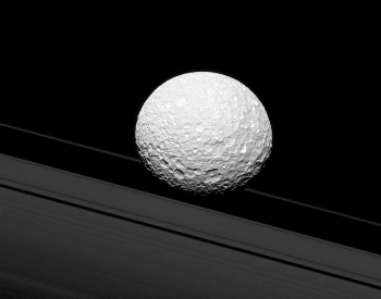A photo of the moon Mimas near two of Saturn's rings
