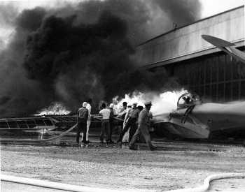 A picture of a PBY patrol bomber on fire after the Pearl Harbor attack