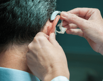 A picture of someone putting on a hearing aid