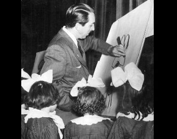 A picture of Walt Disney drawing Goofy for a group of girls