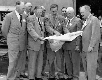 A picture of Walt Disney sharing plans for Disneyland in California